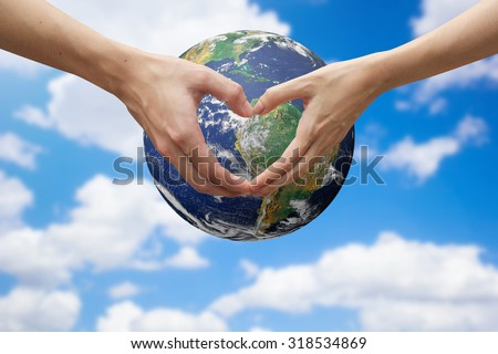 close up male and female hands making heart shape over the global on blur sky.safe the world concept:symbols of human's hands to show that they love the earth.Elements of this image furnished by NASA - stock photo