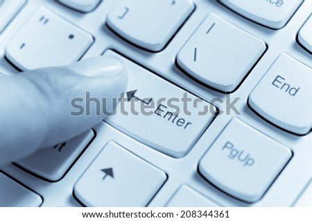Close up Male hand finger press enter computer keyboard button (Over blue color) - stock photo