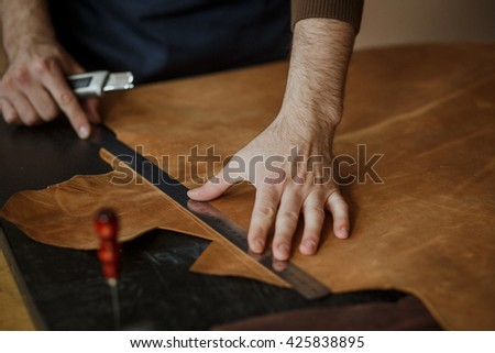 Close-up. Male hand master cut with a knife to skin products. Small business