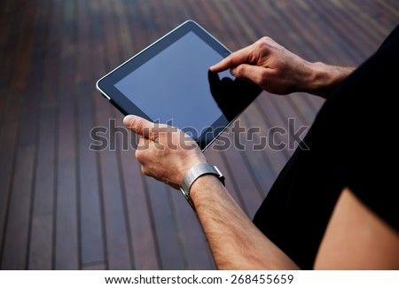 Close up male hands finger touching blank screen touch pad against wooden background, freelancer man working on digital tablet with copy space, hipster man zooming digital image on touchscreen device - stock photo