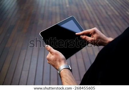 Close up male student hands using blank screen touch pad against wooden background, freelancer man working on digital tablet with copy space, hipster man zooming digital image on touchscreen device - stock photo