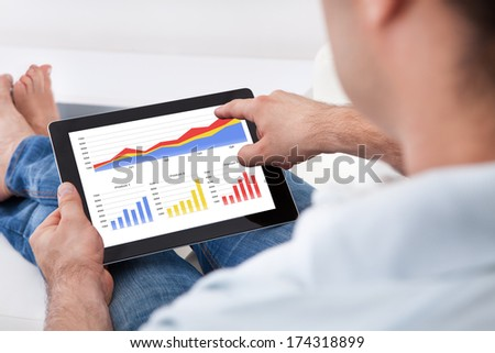 Close-up Man Analyzing Financial Statistics Displayed On The Tablet Screen - stock photo