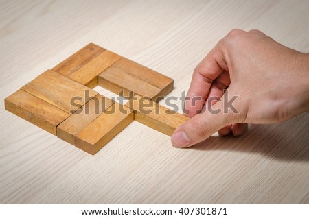 Close up Man hand holding a missing piece in a square tangram puzzle, business success concept. - stock photo