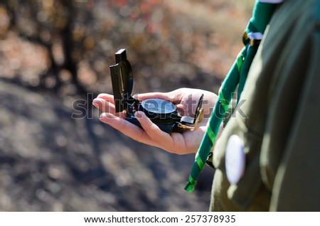 Close up Man Hand Holding Compass Device to Find Direction at the Camping Area. - stock photo