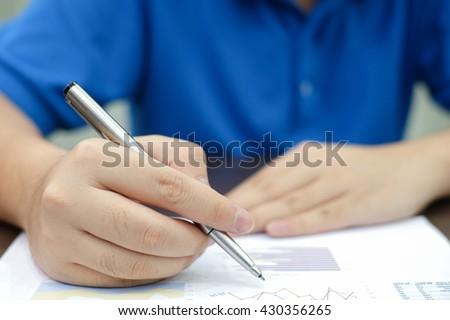 close up man hand with pen signing on paper application:student doing examination in the class:education and business concept.