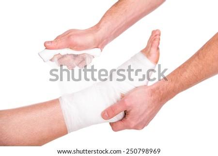 Close-up man is putting bandage on injured feet. - stock photo
