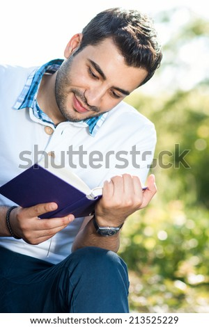 Close up man reading book, outdoors, outside - stock photo