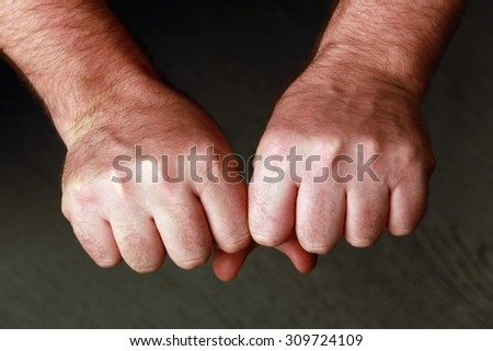 close-up man's fist on a gray background studio  - stock photo