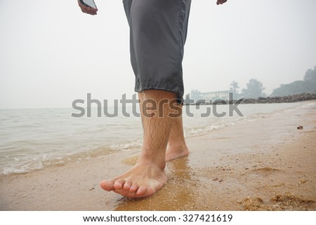 Close up man walking barefoot on white sand beach.Selective focus                                - stock photo