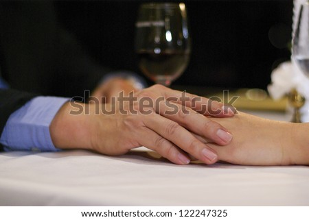 Close up mate lover hand on table in luxury restaurant - stock photo