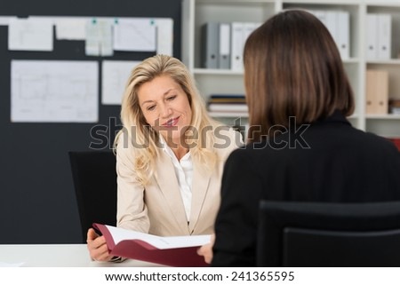 Close up Mature Businesswoman with Blond Hair Discussing Business Matter to her Assistant with Reference Document at her Office. - stock photo
