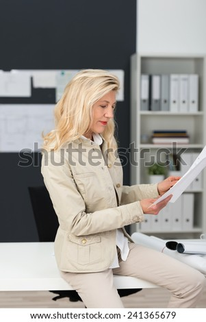 Close up Mature Businesswoman with Blond Hair Reviewing Documents Seriously at the Office while Sitting at her White Working Table. - stock photo