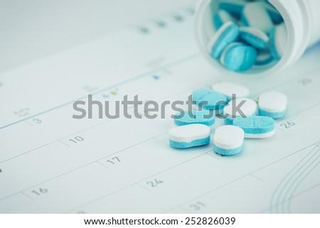 Close up Medicine pills on calendar - stock photo