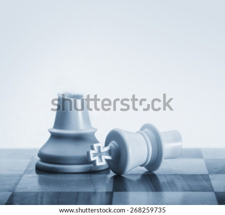Close up metaphor of broken king on chess board - stock photo