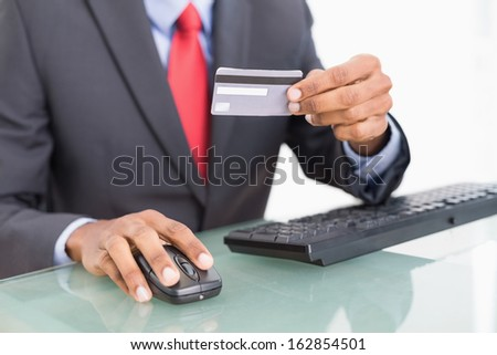Close up mid section of a businessman doing online shopping through computer and credit card - stock photo