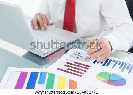 Close-up mid section of a businessman with laptop and graphs sitting at office desk