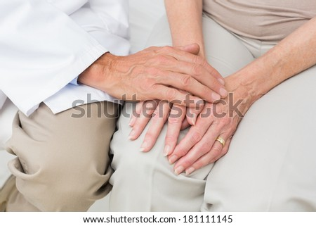 Close-up mid section of a female senior patient visiting a doctor at the medical office - stock photo