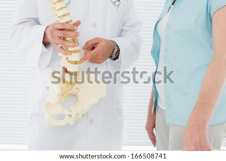 Close-up mid section of a male doctor explaining the spine to a patient in medical office - stock photo