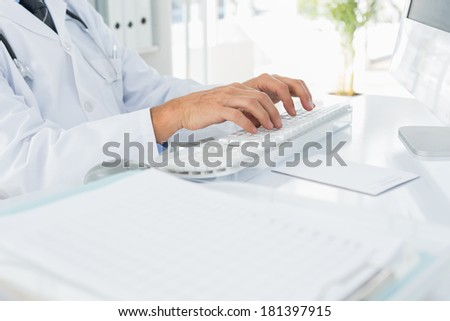 Close-up mid section of a male doctor using computer keyboard at medical office - stock photo