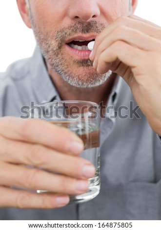 Close-up mid section of a man with glass of water and pill - stock photo