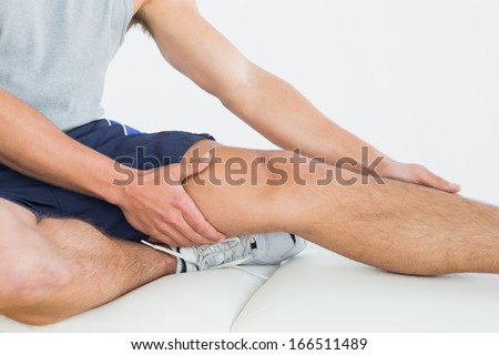 Close-up mid section of a man with his hands on a painful leg - stock photo
