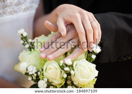 Close-up mid section of a newlywed couple with wedding rings and bouquet - stock photo