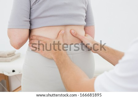 Close-up mid section of a physiotherapist examining woman's back in the medical office - stock photo