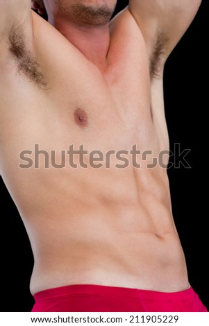 Close-up mid section of a shirtless muscular man standing over black background