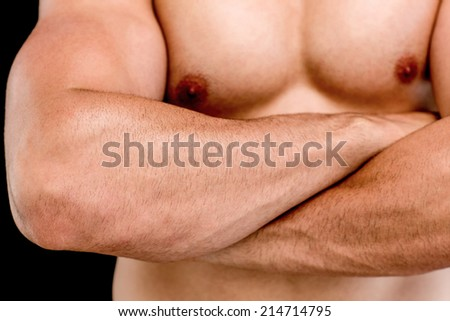 Close-up mid section of a shirtless muscular man with arms crossed over black background