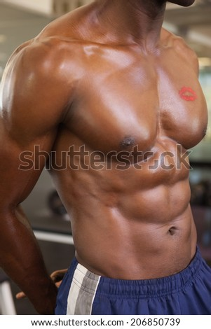 Close-up mid section of a shirtless muscular man with lipstick mark on chest - stock photo