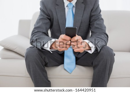 Close-up mid section of a well dressed man text messaging on sofa in living room at home - stock photo