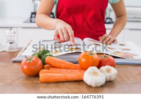 Close-up mid section of a woman with recipe book and vegetables in the kitchen at home - stock photo