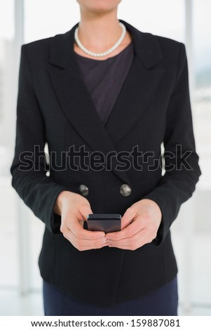 Close-up mid section of a young elegant businesswoman in suit holding a cellphone