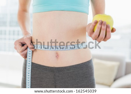 Close up mid section of a young woman measuring waist as she holds apple in fitness studio - stock photo