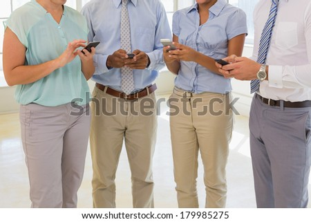 Close-up mid section of business colleagues text messaging in the office - stock photo