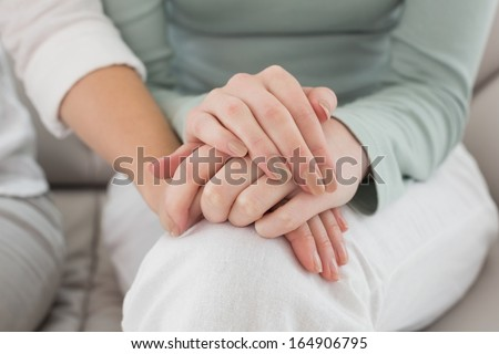 Close-up mid section of female friends touching hands at home on the couch - stock photo