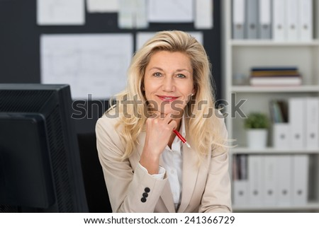 Close up Middle Age Blond Office Woman Sitting at her Work Table Smiling at Camera with One Hand on the Chin. - stock photo