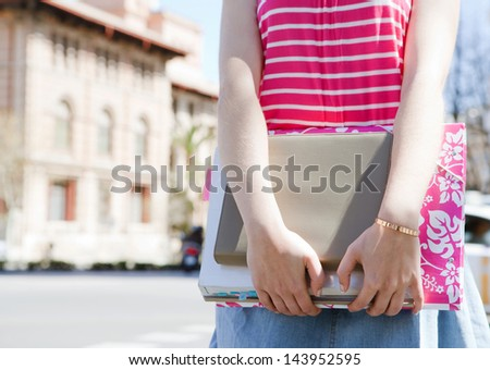 Close up middle section view of a teenager student carrying homework, books and note pads while standing near a college university building in a campus during a sunny summer day. - stock photo