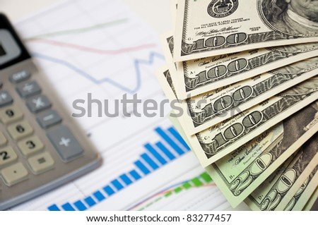 Close-up money against the stock chart and a calculator. - stock photo