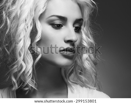 close-up monochrome portrait of young beautiful woman.Blond girl. Curly hairstyle