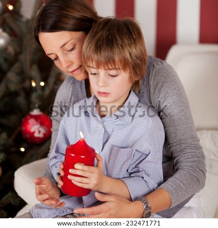 Close up Mother and Son Sitting on the Couch Holding Lighted Red Big Candle for Christmas. - stock photo