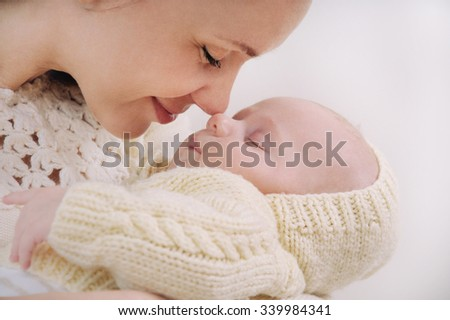 close up mother's face touching nose by nose of her baby; happy family concept; sleeping cute baby; maternity concept; mother and her newborn baby - stock photo