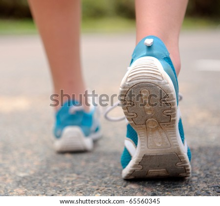 Close up motion shot of person walking away in running shoes