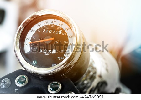 close-up motorcycle speedometer with chrome ring, soft focus and lens flare - stock photo