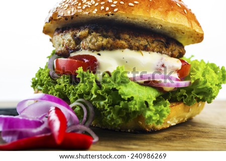Close up Mouth Watering Hamburger with Lettuce, Tomatoes, Onions and Cream on Wooden Table with Onion Rings and Red Pepper. - stock photo