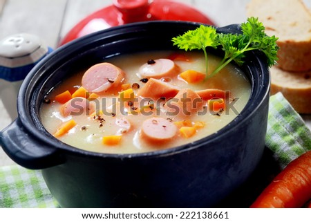 Close up Mouth Watering Hot Creamy Soup Dish with Sausage on Cloth at Wooden Table.