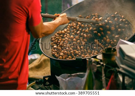 Close up movement hand a man worker roasting chestnuts in street chinatown or Yaowarat Road in Bangkok, Thailand - stock photo
