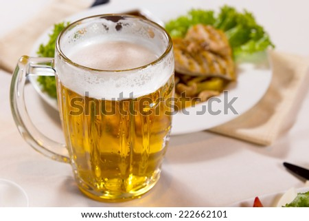 Close up Mug of Beer Beside Main Dish on White Table - stock photo
