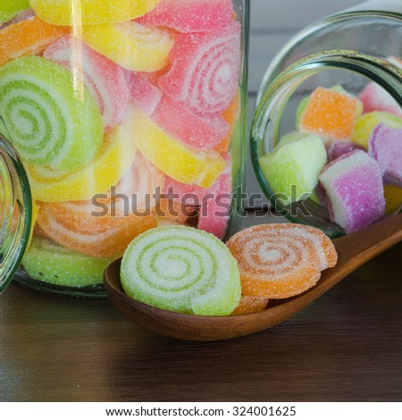 Close-up Multi colour candies on wooden spoon - stock photo
