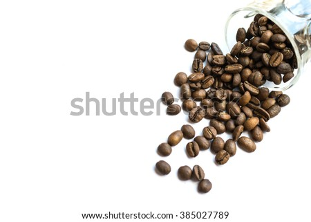 close up multiple roasted coffee beans poured from clear glass on white background